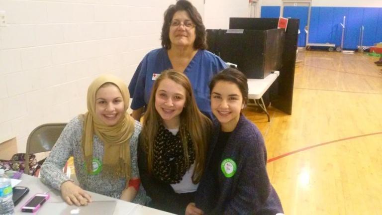 (PHOTO: l-r front row:  Unity Center volunteers Maya Al-Saghir, Ila Sayed, and Tala Saghir. Behind them, Red Cross nurse Kathy Hellen)