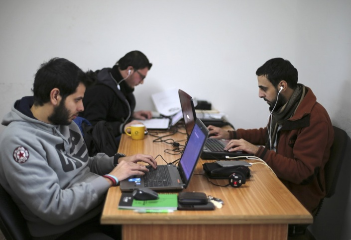 (PHOTO: Palestinian employees process data on their laptops at Unit One in Gaza City January 15, 2015. Picture taken January 15, 2015. REUTERS/Mohammed Salem)