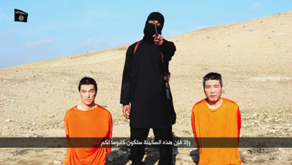 A masked person holding a knife speaks as he stands in between two kneeling men in this still image taken from an online video released by the militant Islamic State group