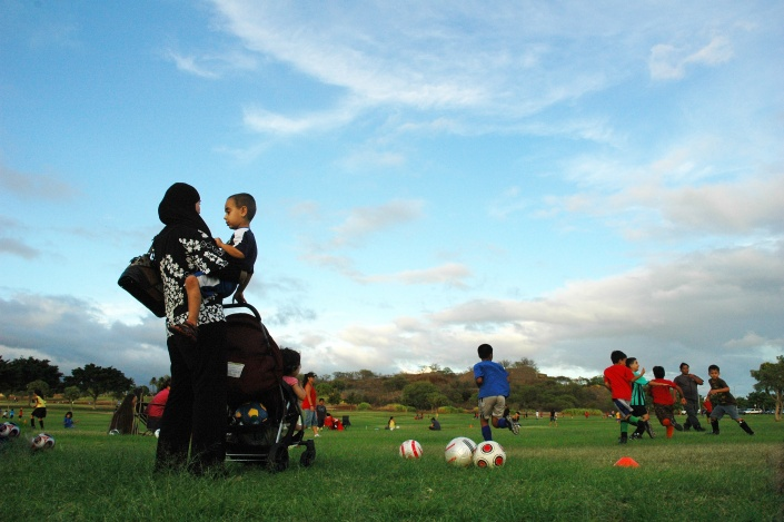 A mother and her children observer a soccer practice in Kapolei, Hawaii. Photo Credit: Keoni Cabral/Flickr