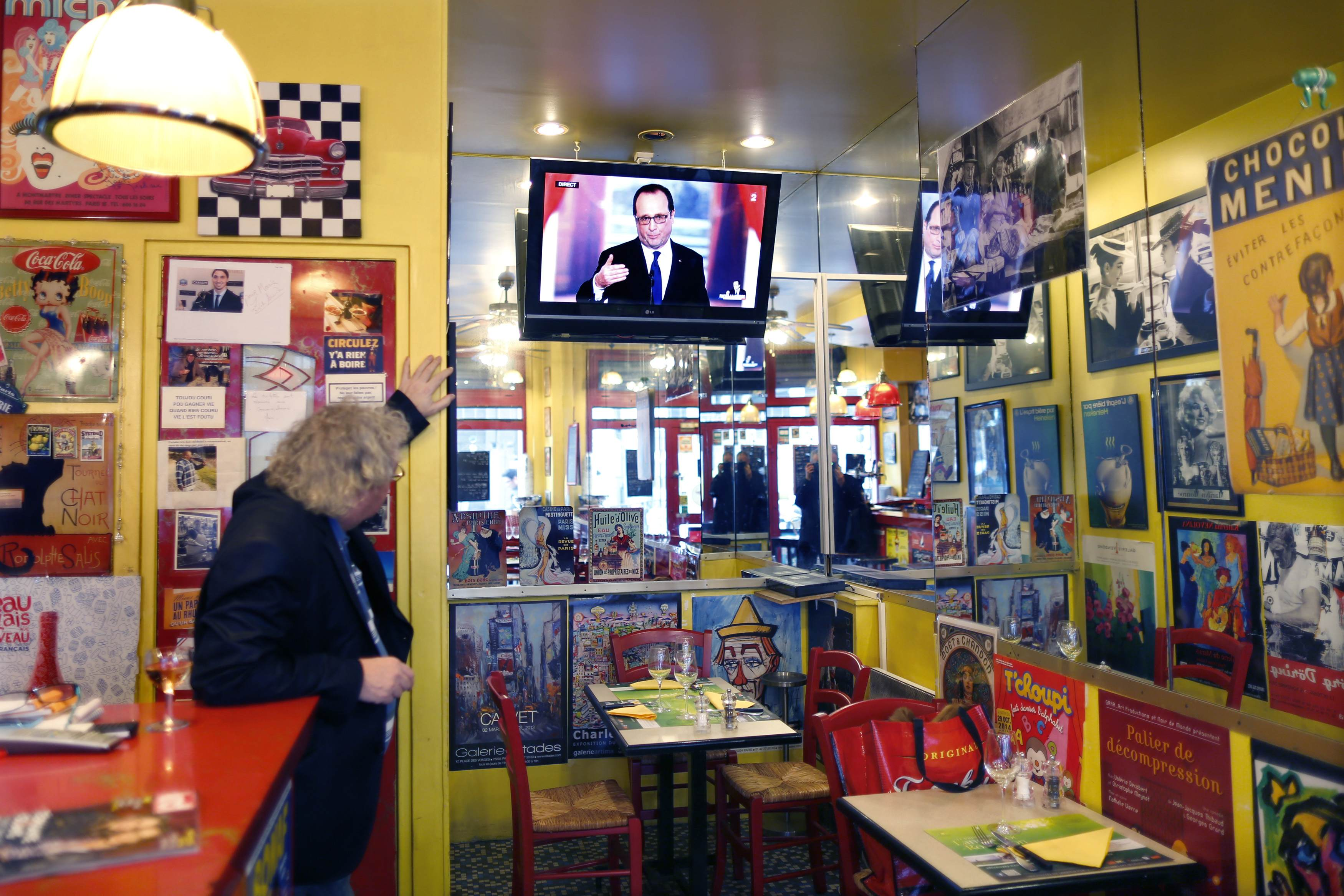 A customer looks at a television screen in a Parisian bistrot as French President Francois Hollande speaks during a news conference at the Elysee Palace in Paris February 5, 2015. Hollande, whose popularity has risen on the back of his handling of the Charlie Hebdo attacks, is expected to make announcements on plans for a new voluntary civilian service for school-leavers and to address the sense of alienation in France's poor suburbs. His comments on efforts to reach a new debt deal between Greece and EU partners will also be closely watched. REUTERS/Charles Platiau