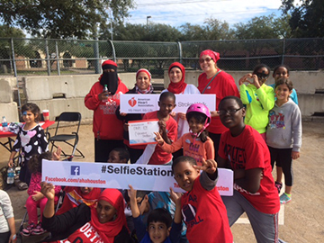 Photo caption: Hammad, third from left in rear, has been hard at work volunteering her time in the Houston area.