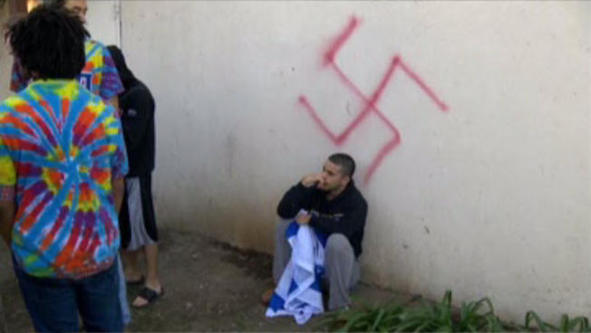 A student with an Israeli flag sits underneath a swastika painted on Alpha Epsilon Pi fraternity discovered on Jan. 31. Photo Credit: KCRA