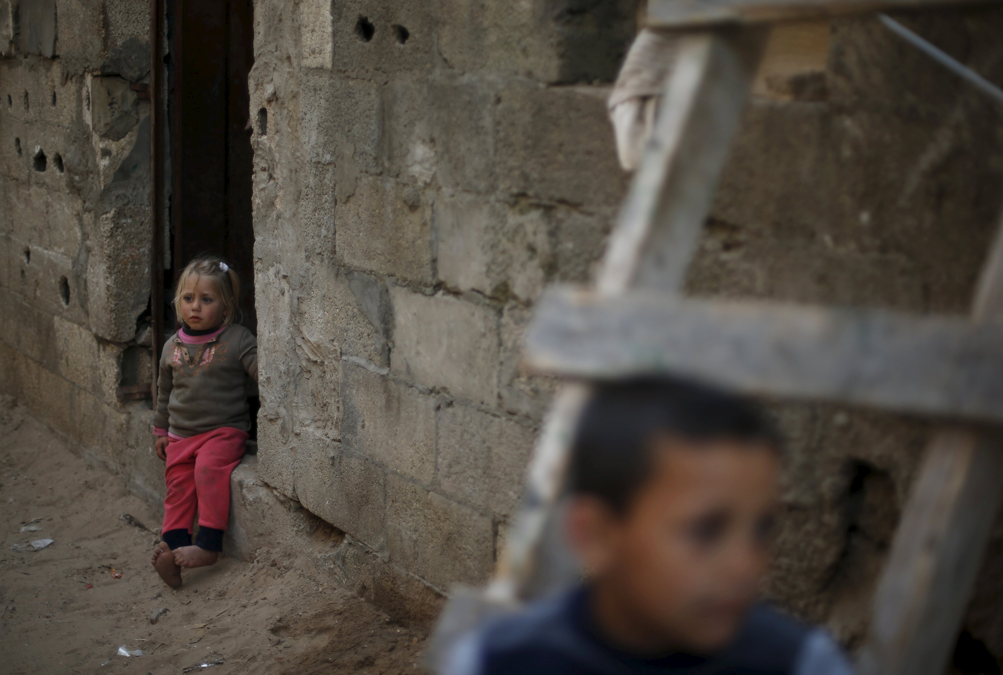 A Palestinian girl sits at the entrance of her family's house in Biet Lahiya, Gaza, March 24. Mohammed Salem/Reuters.
