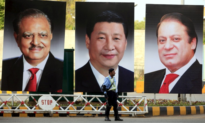 A policeman stands guard next to giant portraits of Pakistan's President Hussain, China's President Xi, and Pakistan's PM Sharif, displayed along a road ahead of Xi's visit to Islamabad