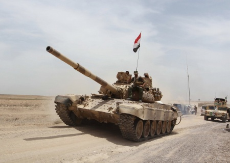 Shi'ite paramilitaries and iraqi army riding on a tank travel from Lake Tharthar towards Ramadi to fight against Islamic state militants. Stringer / Reuters