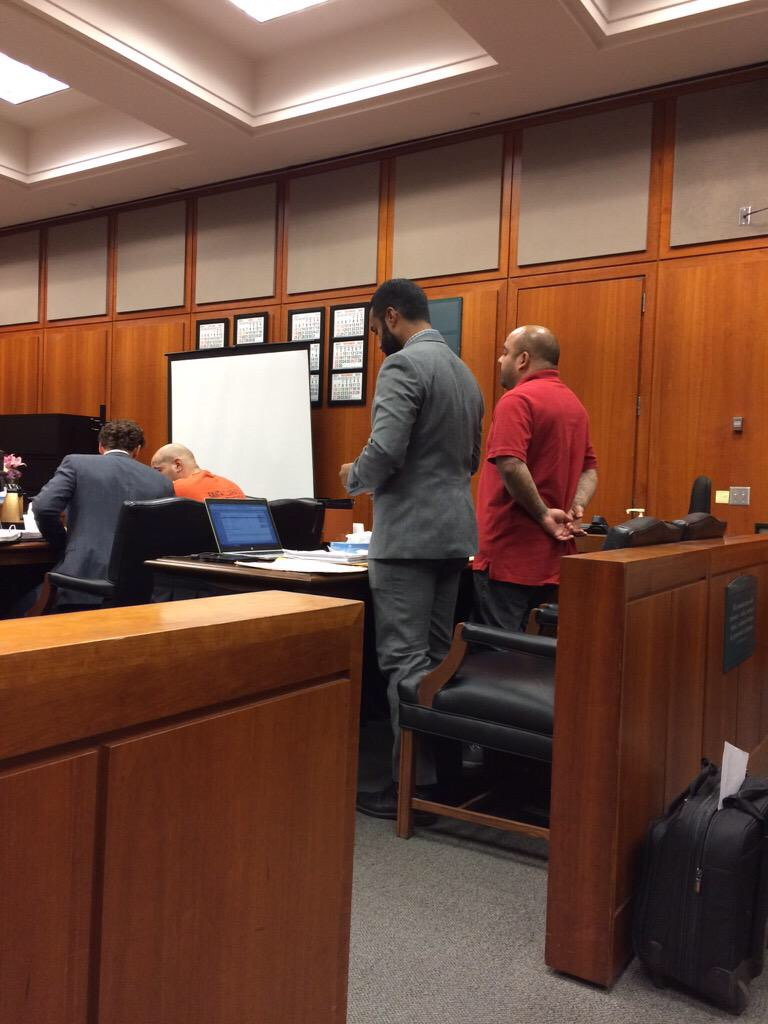 Sajid Khan (center) defending clients in court.