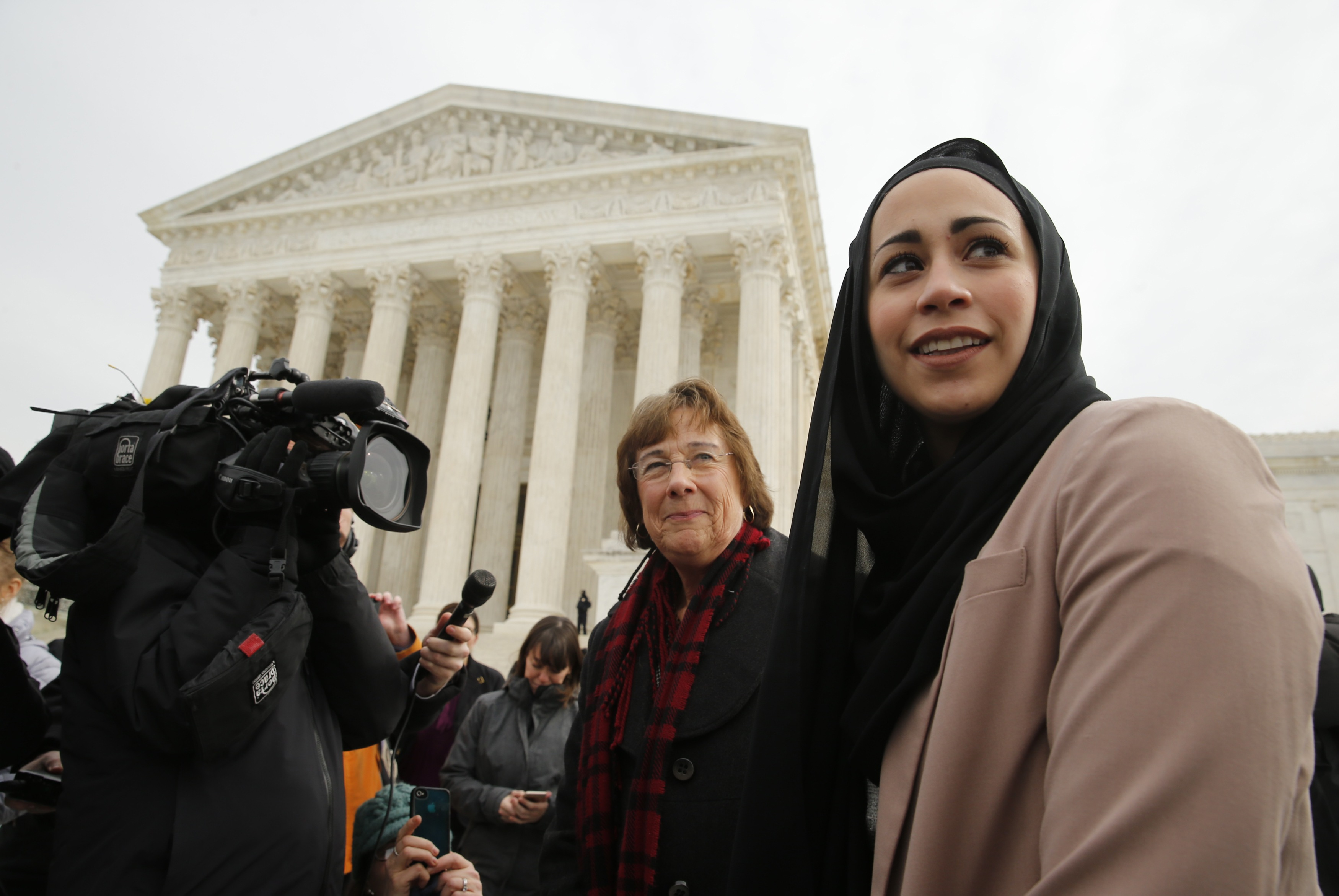Samantha Elauf (R), who was denied a sales job at an Abercrombie Kids store in Tulsa in 2008, stands with U.S. Equal Employment Opportunity Commission (EEOC) lead attorney Barbara Seely (C) at the U.S. Supreme Court in Washington, February 25. REUTERS/Jim Bourg/Files