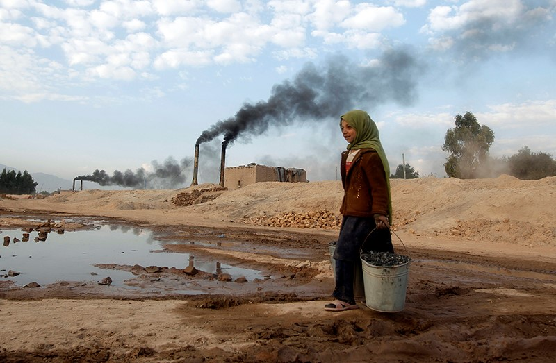 Aisha, 11, carries coal to be used for cooking and heating from a brick-making factory in Jalalabad, Afghanistan, on Dec. 17, 2013. Photo courtesy of Parwiz / Reuters
