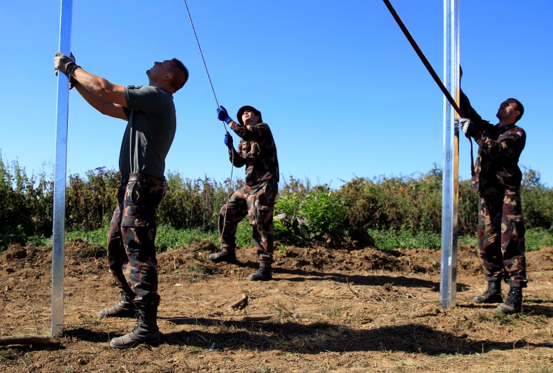 Hungarian soldiers fix the poles of a new fence on the border with Croatia near Beremend, Hungary, September 21, 2015. Bernadett Szabo / Reuters