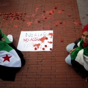 """Women with Syrian opposition flags draped over their shoulders sit next to a sign that reads, """"No to the war. Not Assad. Not ISIS"""", as they take part in a protest in solidarity with the refugees from Syria, in Malaga, southern Spain, September 9, 2015. Jon Nazca / Reuters"""