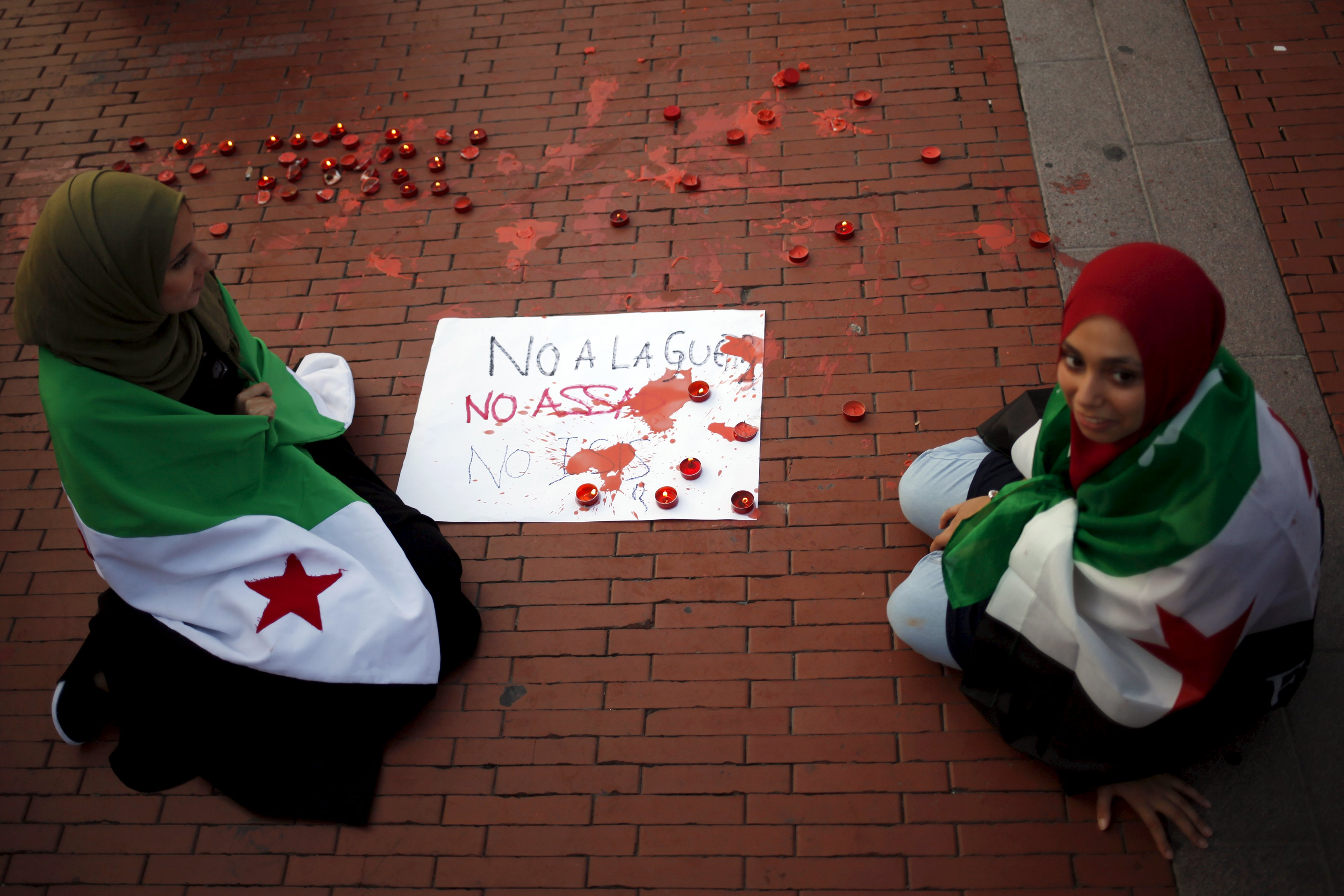 "Women with Syrian opposition flags draped over their shoulders sit next to a sign that reads, ""No to the war. Not Assad. Not ISIS"", as they take part in a protest in solidarity with the refugees from Syria, in Malaga, southern Spain, September 9, 2015. Jon Nazca / Reuters"