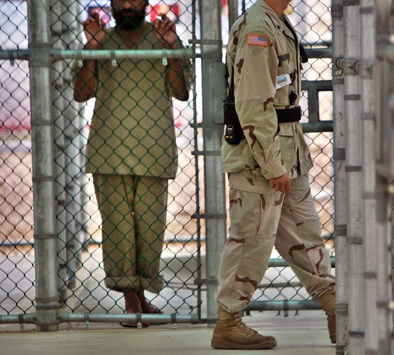 In this photo reviewed by U.S. military officials, a detainee whose name, nationality and facial identification are not permitted holds onto a fence as a U.S. military guard walks past the grounds of the maximum-security prison at Camp 5 in the Guantanamo Bay U.S. Naval Base on June 26, 2006. Photo courtesy of REUTERS