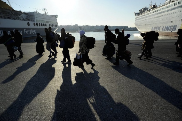Refugees and migrants walk after disembarking from the passenger ferry Eleftherios Venizelos from the island of Lesbos at the port of Piraeus, near Athens, Greece, December 26, 2015. REUTERS/Michalis Karagiannis