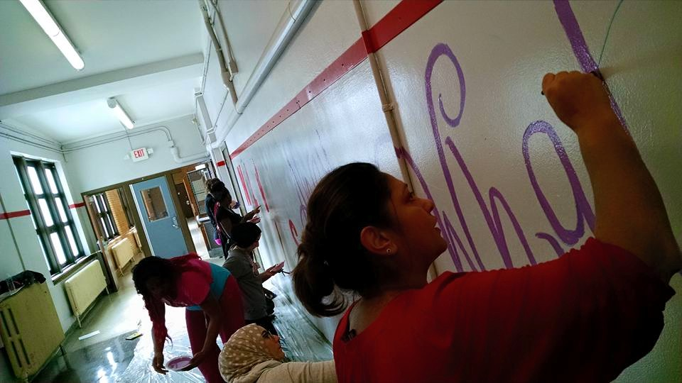 Uzma Khan working on the joint mural at Detroit's Nolan Elementary-Middle School