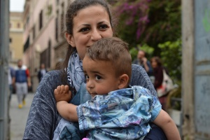 The youngest Syrian refugee aboard the papal plane was two-year-old Riyad, carried here by his mother Nour. Religion News Service photo by Rosie Scammell