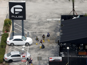 Federal Bureau of Investigation (FBI) officials walk through the parking lot of the Pulse gay night club, the site of a mass shooting days earlier, in Orlando, Florida, on June 15, 2016. Photo courtesy of REUTERS/Adrees Latif
