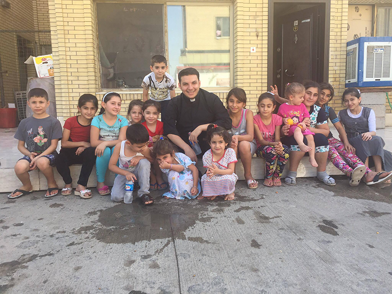 Priest Martin Banni with a group of displaced children from the Christian towns in Nineveh in Erbil. Banni spent much time playing with children, and telling them stories from the Bible. Photo courtesy of Martin Banni